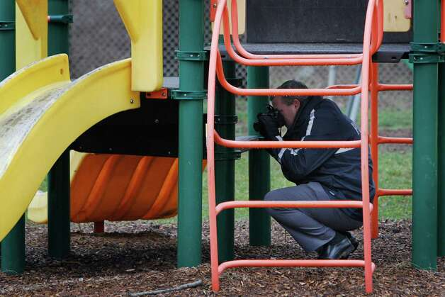 Police investigate the playground in Upper Darby, Pa., where a 5-year-old girl wearing only a T-shirt was found hiding under a piece of playground equipment early Tuesday morning. The girl had been abducted Monday morning from the William C. Bryant School, in west Philadelphia, by a woman claiming to be her mother. (AP Photo/Philadelphia Daily News, Alejandro A. Alvarez) Photo: AP
