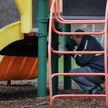 Police investigate the playground in Upper Darby, Pa., where a 5-year-old girl wearing only a T-shirt was found hiding under a piece of playground equipment early Tuesday morning. The girl had been abducted Monday morning from the William C. Bryant School, in west Philadelphia, by a woman claiming to be her mother. (AP Photo/Philadelphia Daily News, Alejandro A. Alvarez)