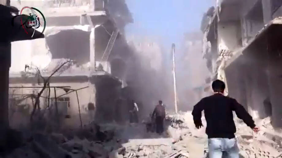 In this photo taken from video obtained from the Shaam News Network, which has been authenticated based on its contents and other AP reporting, Syrian men run to aid injured people in the aftermath of a strike by Syrian government warplanes on the residential neighborhood of Maadamiyeh south of Damascus, Syria, on Monday.  A Syrian airstrike slammed into a house in a rebellious suburb of Damascus early Monday, killing at least a dozen people including eight children, activists said, as President Bashar Assad's regime ramped up its operations against the opposition strongholds ringing the capital. Photo: AP