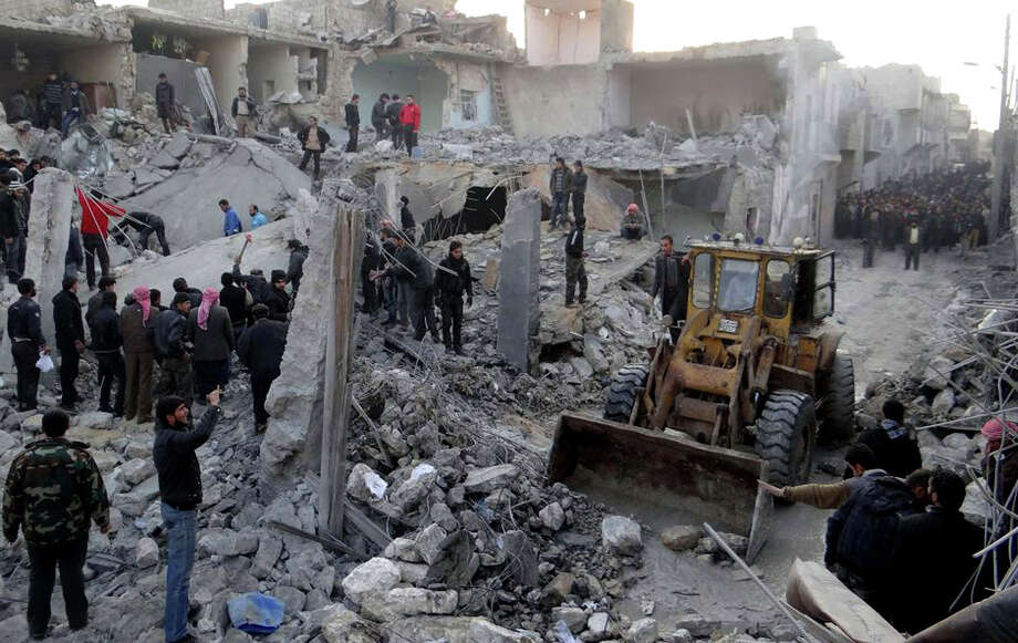 In this citizen journalism image taken on Monday provided by Aleppo Media Center AMC which has been authenticated based on its contents and other AP reporting, people gather around destroyed buildings after airstrikes hit areas in Aleppo, Syria. Photo: AP