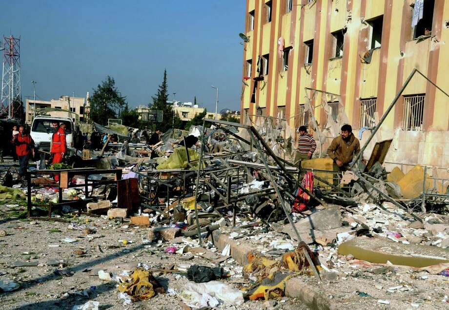 In this photo released by the Syrian official news agency SANA, Syrian people gather at the site after an explosion hit a university in Aleppo, Syria, on Tuesday. Two explosions struck the main university in the northern Syrian city of Aleppo on Tuesday, causing an unknown number of casualties, state media and anti-government activists said. There were conflicting reports as to what caused the blast at Aleppo University, which was in session Tuesday. Photo: AP
