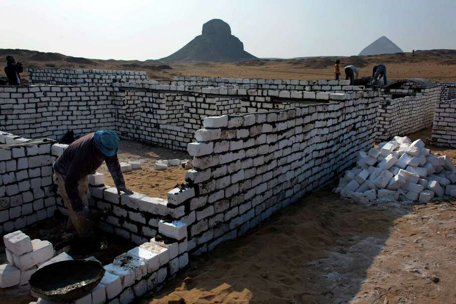 Egyptian labors work last Sunday at the new construction site of the illegal expansion of a local cemetery that is seen spreading toward Egypt's first pyramids and temples, at the ancient historic site of Dahshour, Egypt. Photo: AP