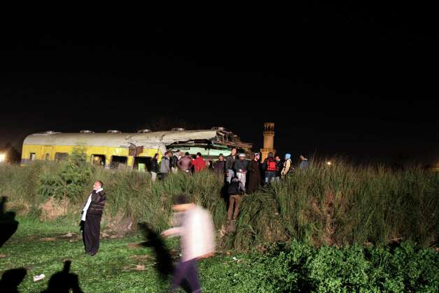 Egyptians try to help rescue injured passengers following a train crash in Badrasheen, 40 KM south of Cairo, Egypt, on Tuesday. At least 19 people died and more than 100 were injured when two railroad passenger cars derailed just south of Cairo, health officials say. The accident comes less than two weeks after a new transportation minister was appointed to overhaul the rail system, and just two months after a deadly collision between a train and school bus. Photo: AP