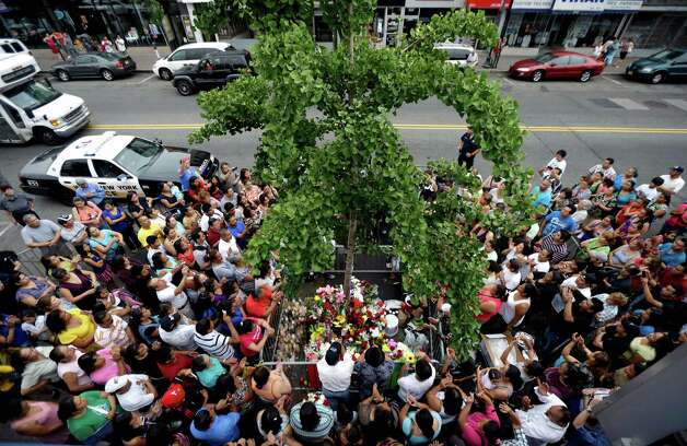People gather around a tree in 2012 where believers say the image of the Virgin of Guadalupe appeared on the tree's trunk as a Mariachi band serenades the Virgin in West New York, N.J.  Believers, who pray in front of the tree nightly, say the outline of the Virgin of Guadalupe appeared on the tree on July 5, 2012, and they are collecting money in hopes of building a glass shrine to protect the image. Photo: AP