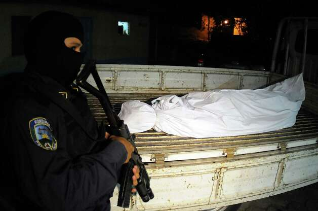 A Honduras national police officer stands guard next to the body of a man that was killed after a raid that seized 772 pounds of cocaine at the naval base in Tegucigalpa, Honduras, on Wednesday. A Jamaican man suspected of drug trafficking has died in the first Honduran anti-narcotics raid on a small boat about 2.5 miles off Honduras' northern coast using U.S. intelligence following a five-month suspension of radar sharing. Another man of Jamaican nationality was arrested. Photo: AP
