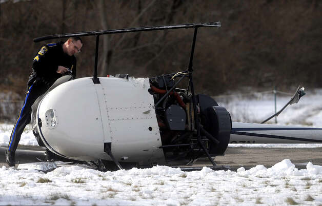 Sgt. Patrick Sweeney with the Connecticut State Police, looks inside a helicopter that rolled onto it's side after a hard landing on the runway on Thursday at Ellington Airport in Ellington Conn.  The pilot and a student pilot walked away from the aircraft were evaluated by medical personnel at the scene but were not transported to a hospital. The state police requested federal authorities including the FAA  to investigate the incident.  (AP Photo/Journal Inquirer, Jim Michaud) Photo: AP