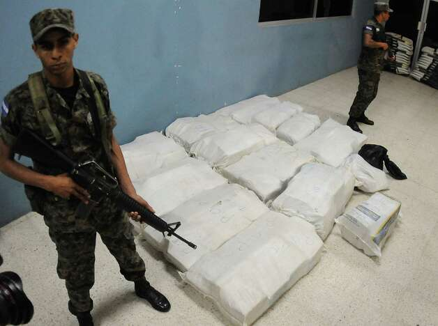 Marines belonging to the Honduras Navy stand guard next to 772 pounds of cocaine at the naval base in Tegucigalpa, Honduras, on Wednesday. A Jamaican man suspected of drug trafficking has died in the first Honduran anti-narcotics raid on a small boat about 2.5 miles off Honduras' northern coast using U.S. intelligence following a five-month suspension of radar sharing. Another man of Jamaican nationality was arrested. Photo: AP