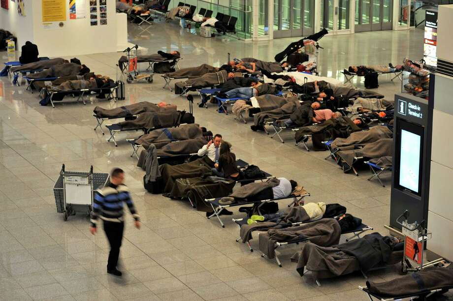 Passengers sleep on camp beds supplied by the authorities in Terminal 2 at Munich Airport, southern Germany, early Friday.  Many flights were canceled due to bad weather conditions and more than a thousand passengers slept rough in the airport due to lack of hotel availability. Photo: AP