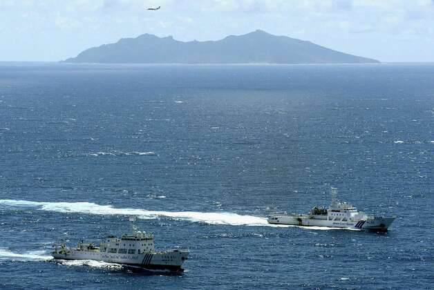 In this Sept. 14, 2012 file photo, Chinese surveillance ship Haijian No. 51, left, and a Japan Coast Guard vessel sail near disputed islands called Senkaku in Japan and Diaoyu in China, seen in the background, in the East China Sea. A high-level Chinese official has called for talks with Japan over the disputed island chain, in an apparent attempt by Beijing to cool tensions that have seen both sides scramble jet fighters to the area in recent days. Jia Qinglin, the head of China's top political advisory body, made the gesture at a meeting in Beijing with former Japanese Prime Minister Yukio Hatoyama, the official China Daily newspaper reported Thursday, Jan. 17, 2013. (AP Photo/Kyodo News, File)  Photo: AP