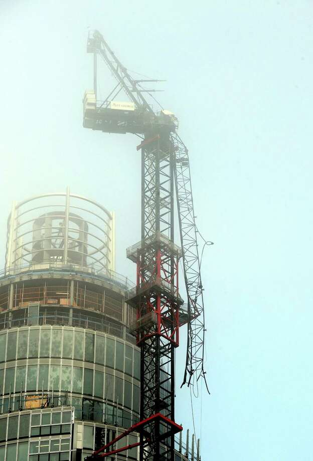 A general view of the damaged crane on top of St Georges Tower close to the scene where a helicopter crashed in central London on Wednesday. Police say two people were killed when a helicopter crashed Wednesday during rush hour in central London after apparently hitting a construction crane on top of a building. (AP Photo/PA, John Stillwell)  Photo: AP