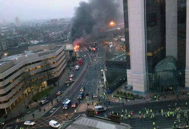In this overhead view showing smoke and flames at the site of a helicopter crash in central London, as people gather to view the scene shortly after the incident, early Wednesday. Police say two people were killed when a helicopter crashed during rush hour in central London after apparently hitting a construction crane on the side of St. George's Tower. This photo was taken from an adjacent building to St. George's Tower which is out of shot right, and construction workers are seen gathering below right.  (AP Photo / Victor Jimenez, PA) Photo: AP