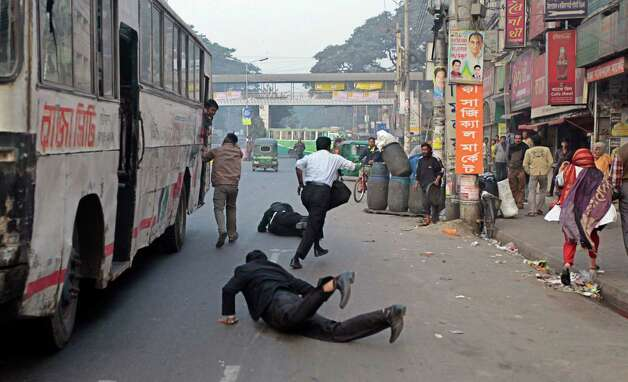 Scared passengers jump off a bus as activists of left parties threaten them with dire consequences during a half-day strike in Dhaka, Bangladesh, Wednesday. A combination of three left parties, including Communist Party of Bangladesh, called for the strike to protest against an oil price hike. Photo: AP