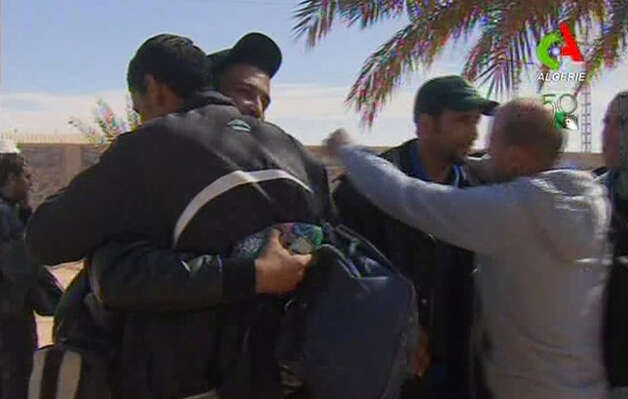 Rescued hostages hug each other  in Ain Amenas, Algeria, in this image taken from television  Friday. Algeria's state news service says nearly 100 out of 132 foreign hostages have been freed from a gas plant where Islamist militants had held them captive for three days.  The APS news agency report was an unexpected indication of both more hostages than had previously been reported and a potentially breakthrough development in what has been a bloody siege. (AP Photo/Canal Algerie  via Assiaciated Press TV) Photo: AP