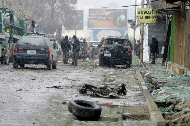 A security official with the Afghan intelligence services, center, investigates the scene of a suicide car bomb attack in Kabul, Afghanistan, Wednesday. Six militants - one driving a car packed with explosives - attacked the gate of the Afghan intelligence service in the capital Kabul on Wednesday, setting off a blast that could be heard throughout downtown and which sent a plume of dark smoke rising into the sky. Photo: AP