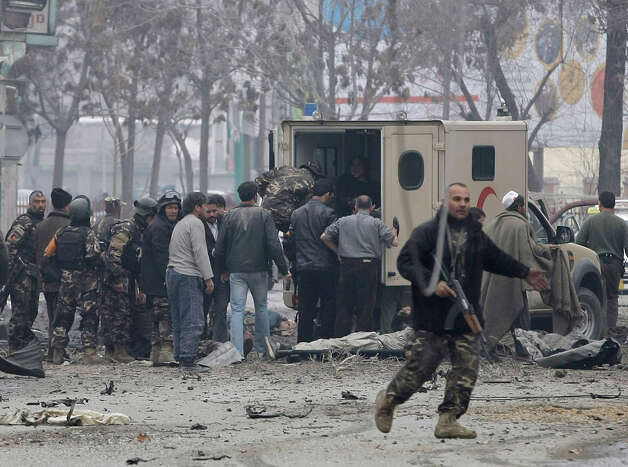 Afghans load victims into an ambulance at the scene of a suicide car bomb attack in Kabul, Afghanistan, Wednesday. Six militants - one driving a car packed with explosives - attacked the gate of the Afghan intelligence service in the capital Kabul on Wednesday, setting off a blast that could be heard throughout downtown and which sent a plume of dark smoke rising into the sky. Photo: AP