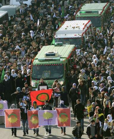 Masked men hold PKK flags as they walk in front of the coffins of three Kurdish activists as tens of thousands of people gather for their funeral in Diyarbakir, sourtheastern Turkey, Thursday. The three women activists, including a founding member of the outlawed Kurdistan Workers' Party, or PKK, were found shot dead in Paris last week at a time when Turkey is holding peace talks with the rebels' jailed leader. Many believe the killings may be an effort to derail the talks. Photo: AP