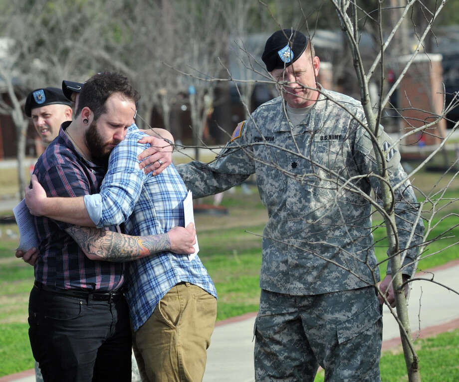 Joey Swindle, left, comforts John Swindle as they mourn the loss of their brother, Sgt. Jason Swindle, after an Eastern Red Bud tree was dedicated in his honor along the Warrior's Walk in Fort Stewart, Ga. Thursday morning. Sgt. Swindle was killed in September while serving in Afghanistan. (AP Photo/The Morning News, Richard Burkhart) Photo: AP