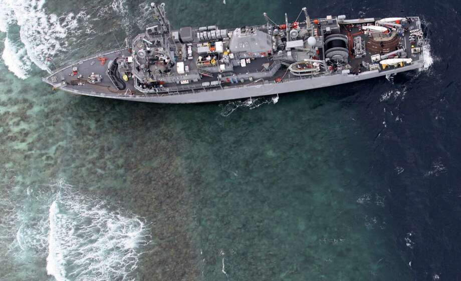 The USS Guardian, a U.S. Navy minesweeper, ran aground on Thursday off Tubbataha Reef, a World Heritage Site in the Sulu Sea, 400 miles southwest of Manila, Philippines. Most of the sailors left the ship Friday for safety reasons after initial efforts to free the vessel failed, the U.S. Navy said. (AP Photo/Armed Forces of the Philippines Western Command) Photo: AP