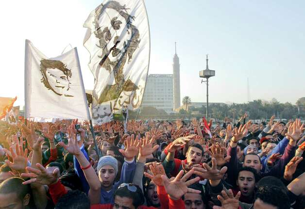 Thousands of soccer fans of Egypt's most popular team, Al-Ahly, march towards Tahrir Square, the focal point of the Egyptian uprising, in Cairo, Egypt, Friday. Fans called for revenge a week before a court verdict is expected over last year's Port Said football stadium disaster, which killed 72 fans. Flags show images of some of the victims. Photo: AP