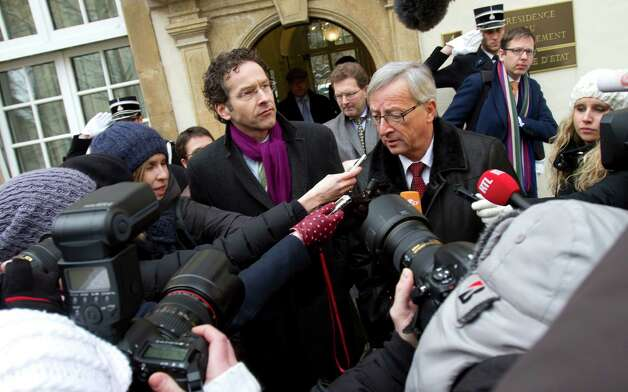 Luxembourg's Prime Minister and head of the eurogroup Jean-Claude Juncker, center right, and Dutch Finance Minister Jeroen Dijsselbloem, center left, speak with the media in Luxembourg on Friday. The outgoing leader of the group of finance ministers from the 17 European Union countries that use the euro is meeting with Jeroen Dijsselbloem on Friday, another indication the Dutch finance minister will take the post next week. Photo: AP