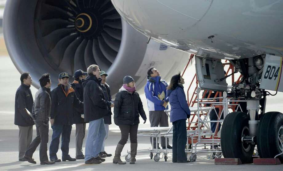 U.S. officials, center,  inspect a All Nippon Airways jet which made an emergency landing Wednesday, at Takamatsu airport in Takamatsu, western Japan, Friday. An official with Japan's transport safety board says four U.S. officials, including two Boeing Co. representatives, have arrived at the airport in western Japan to inspect the troubled Boeing 787 jet. (AP Photo/Kyodo News) Photo: AP