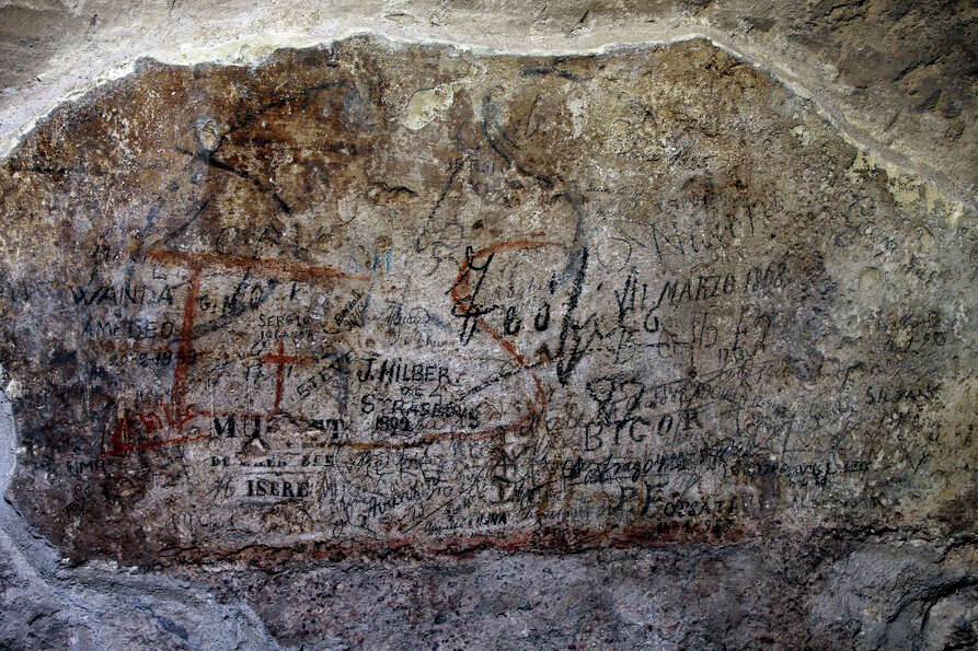 An ancient graffiti, in background red, covered by tourist's graffiti, is seen inside a gallery of R
