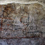 An ancient graffiti, in background red, covered by tourist's graffiti, is seen inside a gallery of Rome's Colosseum, Friday, Jan. 18, 2013.