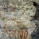 An ancient graffiti recently discovered during restoration works is seen inside a gallery of Rome's Colosseum, Friday, Jan. 18, 2013. A long-delayed restoration of the Colosseum's only intact internal passageway has yielded ancient traces of red, black and blue frescoes - as well as graffiti and drawings of phallic symbols - indicating that the arena where gladiators fought was far more colorful than previously thought. Officials unveiled the discoveries Friday and said the passageway would be open to the public starting this summer, after the - $100,000 restoration is completed. The frescoes were hidden under decades of calcified rock and grime, and were revealed after the surfaces were cleaned. The traces confirmed that while the Colosseum today is a fairly monochrome gray travertine rock, red brick and bits of moss-covered marble, in its day its interior halls were a rich and expensive Technicolor.
