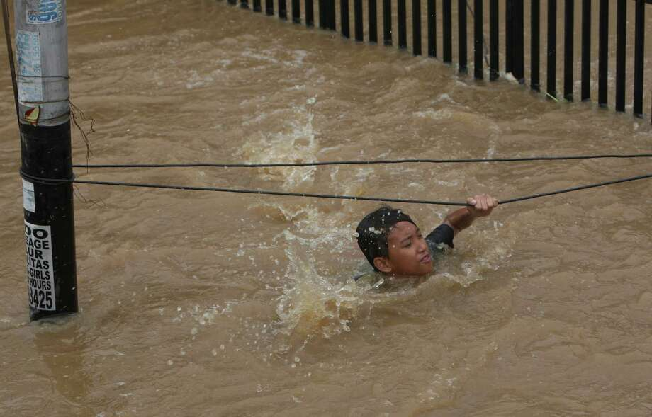 An Indonesian man grabs wires to keep from being swept away by flood water in Jakarta, Indonesia on Friday. Authorities were working Friday to repair a dike that collapsed amid floods that swamped the Indonesian capital as the waters gradually receded from the main streets of the teeming city. Photo: AP