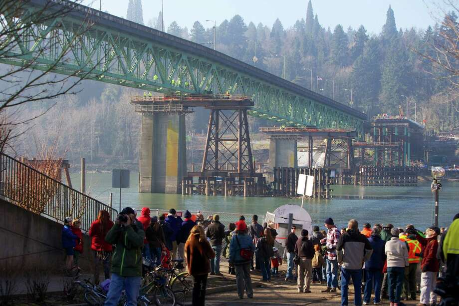People watch the Sellwood Bridge the 87-year-old southeast Portland span move a few yards to aid the construction of its replacement on Saturday in Portland, Ore. (AP Photo/The Oregonian, Randy L. Rasmussen) Photo: AP