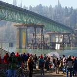 People watch the Sellwood Bridge the 87-year-old southeast Portland span move a few yards to aid the construction of its replacement on Saturday in Portland, Ore. (AP Photo/The Oregonian, Randy L. Rasmussen)