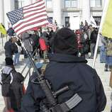 Gun-rights advocate Nate Rodriguez, of West Valley City, Utah, carries his AR-15 with a U.S. flag in the barrel outside the Utah Capitol during the national Gun Appreciation Day Rally on Saturday at the Utah State Capitol, in Salt Lake City.