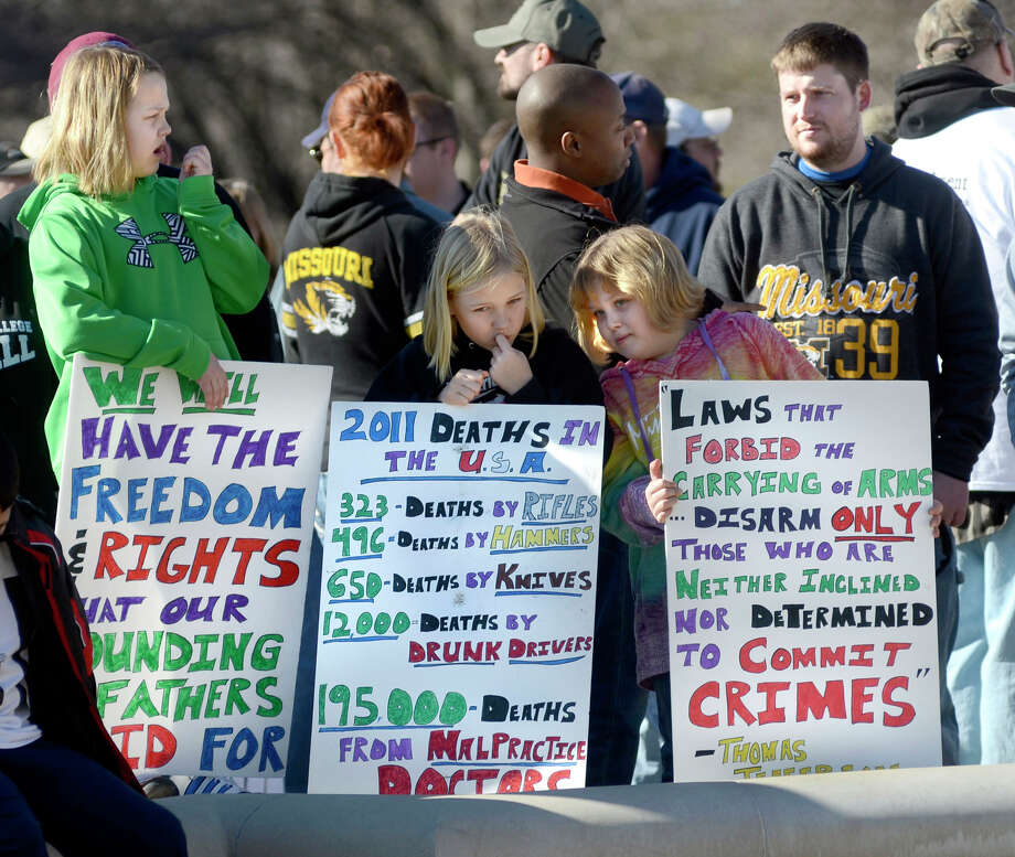 From left, friends Ella Sikes,10, Macey Seabaugh, 9, and Zoe Sikes, 7, from Fredericktown, Mo. each hold signs they made for a gun rights rally outside the capitol building in Jefferson City, Mo. on Saturday. Second Amendment advocates rallied in state capitals nationwide Saturday, days after President Barack Obama unveiled a sweeping package of federal gun-control proposals. Photo: AP