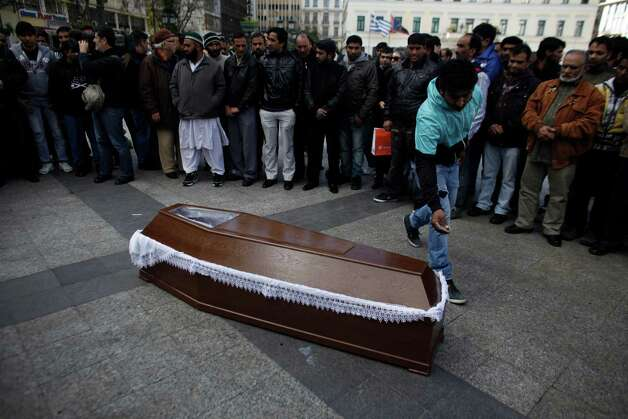 Mourners pray in front of the coffin carrying the body of Shehzad Luqman, a Pakistani immigrant who was murdered on Thursday after being stabbed by suspected extreme rightists, during a ceremony in front of the city Hall in Athens on Saturday. An estimated 3,000 people marched  through central Athens in protest at a spate of anti-immigrant attacks that turned fatal Thursday when a 27-year-old Pakistani immigrant was stabbed by suspected extreme rightists. Photo: AP