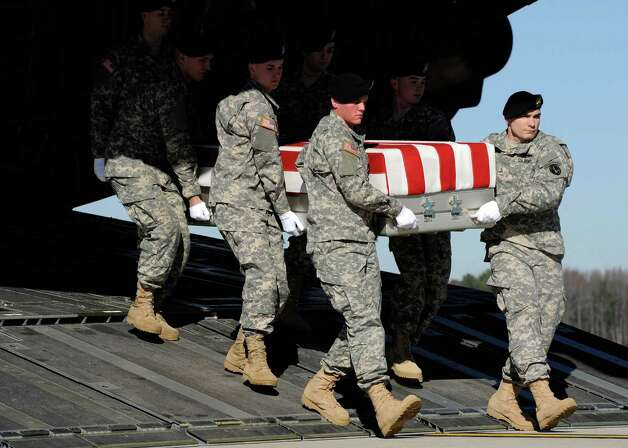 An Army carry team moves a transfer case containing the remains of Sgt. David J. Chambers Saturday at Dover Air Force Base, Del. According to the Department of Defense, Chambers, 25, of Hampton, Va., died Wednesday in the Panjwai district of Kandahar province, Afghanistan, of wounds sustained when he encountered an enemy improvised explosive device while on dismounted patrol. Photo: AP