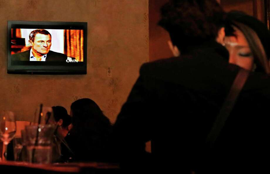 The second night of Oprah Winfrey's interview of former cycling star Lance Armstrong plays on video screens at Pete's Cafe Bar in downtown Los Angeles on Friday. Through a marathon mea culpa that spanned two nights on TV, Armstrong spoke almost dispassionately about lying and cheating, about arrogance and bullying, about lost honor, status, achievement and income. Photo: AP
