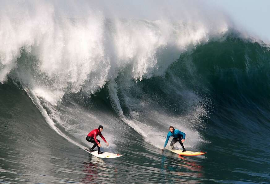 Alex Martins, red, and Shane Desmond ride a wave during the first round of the Mavericks Invitationa
