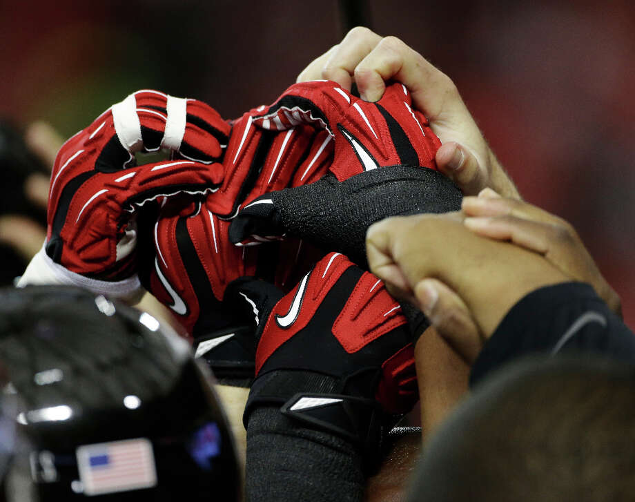 Members of the Falcons join hands before facing the 49ers. Photo: Mark Humphrey