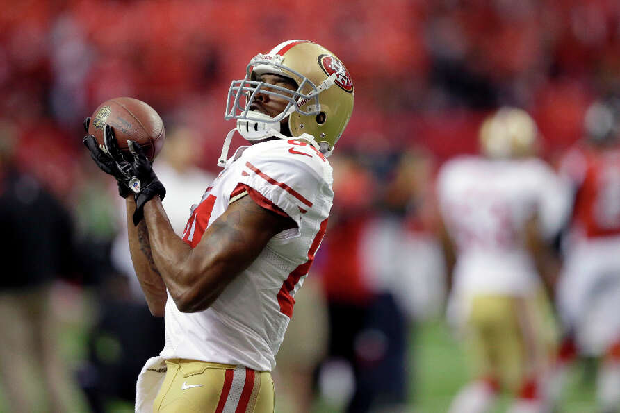 49ers receiver Randy Moss catches a pass while warming up.