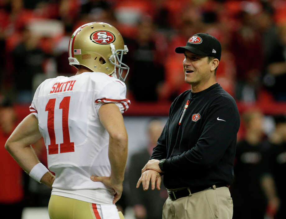 49ers coach Jim Harbaugh speaks with quarterback Alex Smith before the NFC title game. Photo: Dave Martin