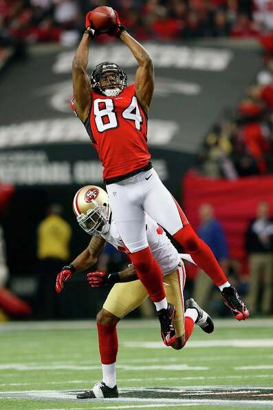 Wide receiver Roddy White #84 of the Atlanta Falcons catches a pass in front of free safety Dashon G