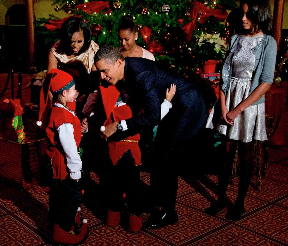 President Barack Obama, center, with, first lady Michelle Obama, back left, and their children Sasha, back center, and Malia, right, greet children dressed like elves at the National Building Museum in Washington, Sunday, Dec. 9, 2012. The first family is attending the taping of the 2012 Christmas in Washington. Photo: Manuel Balce Ceneta, Associated Press / AP