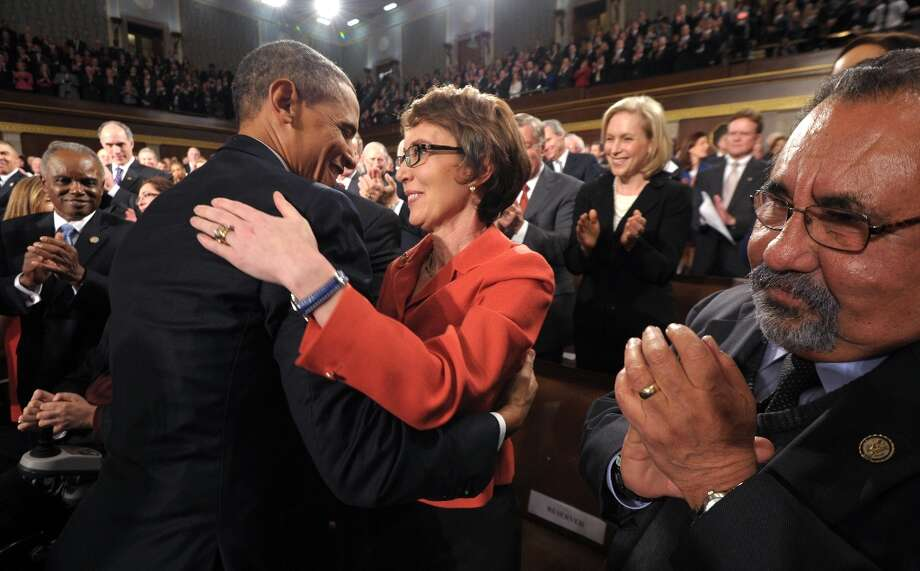 President Barack Obama embraces retiring Rep. Gabrielle Giffords, D-Ariz., as members of Congress applaud before his State of the Union address in front of a joint session of Congress Tuesday, Jan. 24, 2012, on Capitol Hill in Washington. Photo: Saul Loeb, ASSOCIATED PRESS / AP2012