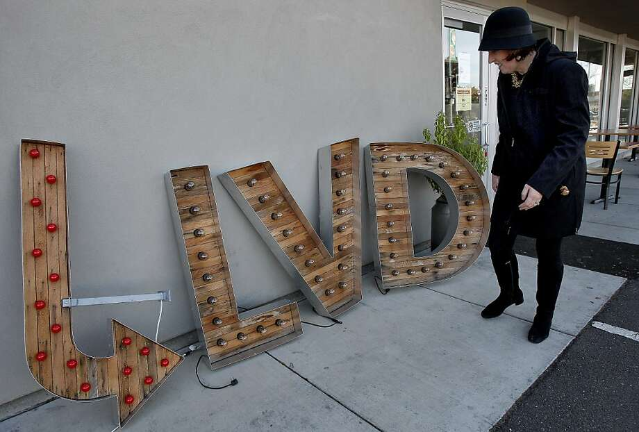 """Roseann Galvan, co-owner of Boulevard Burger in Castro Valley, displays a portion of the restaurant's sign, which she now has in storage after county planners ordered it removed. """"We just wanted to do something unique and fresh,"""" she says. Photo: Brant Ward, The Chronicle"""