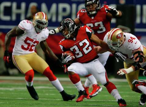 Atlanta Falcons running back Jacquizz Rodgers (32) breaks through an attempted tackle by Defensive tackle Justin Smith (94) and Linebacker Patrick Willis (52) in the first quarter of the San Francisco 49ers game against the Atlanta Falcons in the NFC Championship game at the Georgia Dome in Atlanta, GA., on Sunday January 20, 2013. Photo: Carlos Avila Gonzalez, The Chronicle / ONLINE_YES