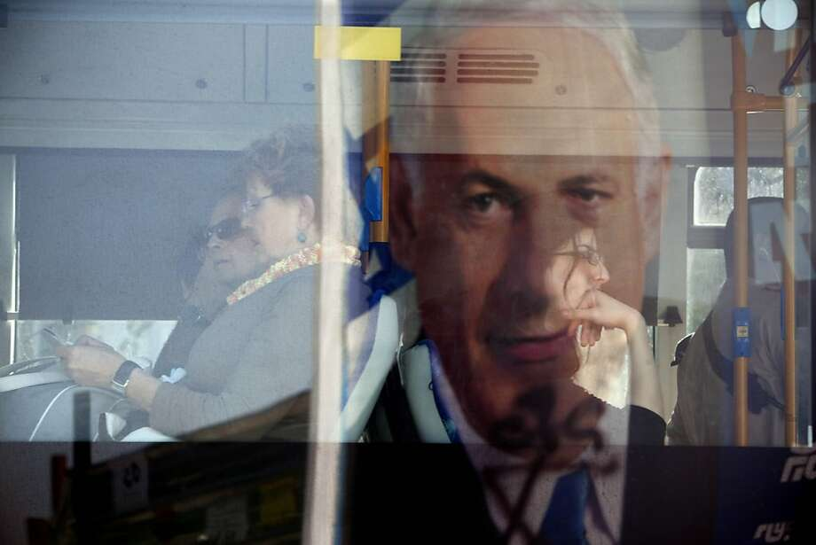 A campaign billboard for Prime Minister Benjamin Netanyahu is reflected in a bus window in Givataim, Israel. The Likud Party leader is expected to win another term. Photo: Oded Balilty, Associated Press
