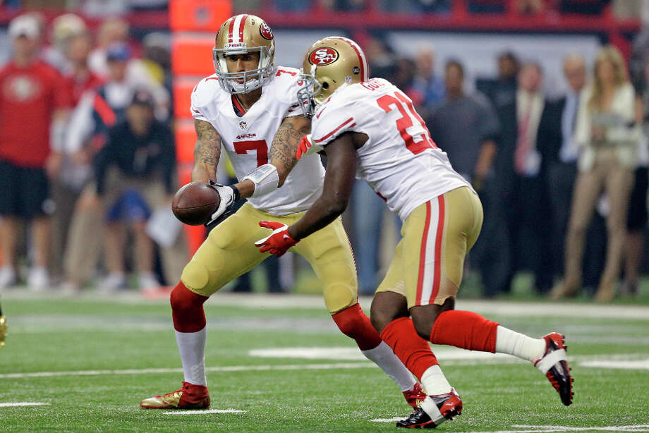 49ers quarterback Colin Kaepernick hands the ball off to running back Frank Gore during the first half. Photo: David Goldman