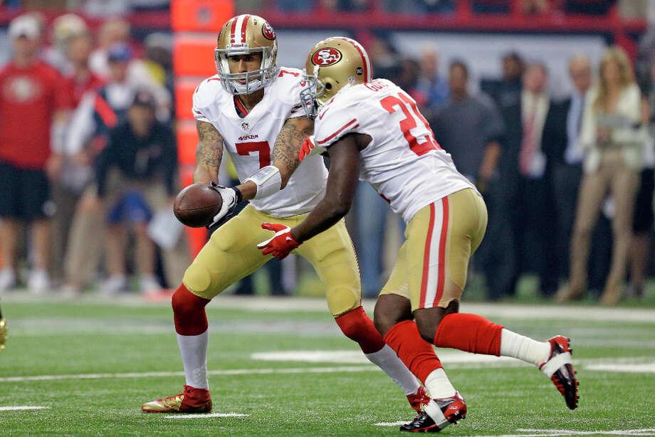 49ers quarterback Colin Kaepernick hands the ball off to running back Frank Gore during the first half. Photo: David Goldman