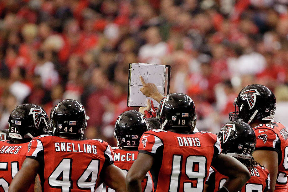 Falcons players look at the playbook during the first half. Photo: Mark Humphrey