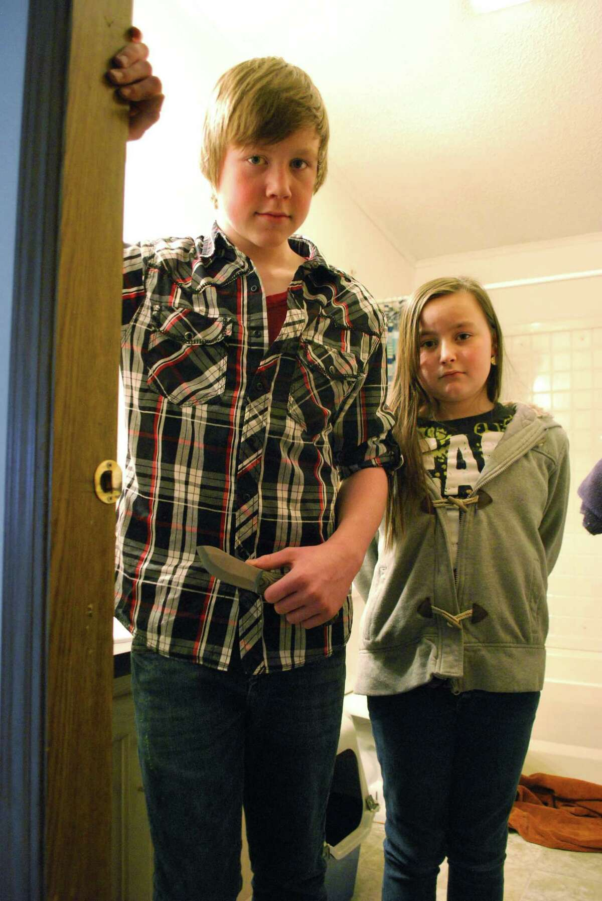 James Persyn III, 14, holds the knife he had on Wednesday night while posing for a picture with his sister Acelin Persyn, 11, a their Shepherd, Mich. home on Friday. Persyn was home alone with his sister and 2-year-old brother when he rescued a Central Michigan University student fleeing from gunman Eric Ramsey, who had earlier kidnapped and raped her.